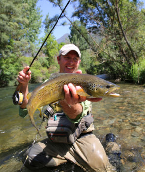 fly-fisherman-holding-brown-trout-in-stream-water