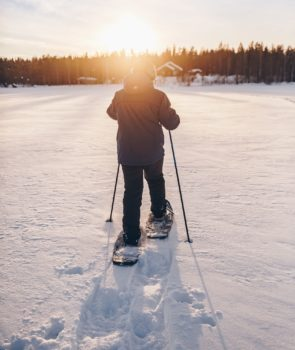man-in-snowshoes-is-walking-with-beautiful-sunrise-light